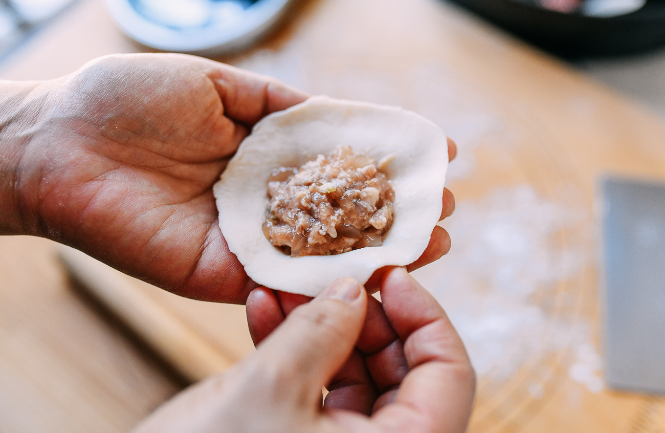 2 tablespoons of shengjian bao filling in center of rolled dough, thewoksoflife.com