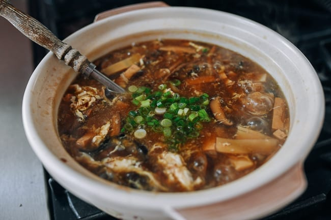 Adding scallion to vegetarian hot and sour soup, thewoksoflife.com