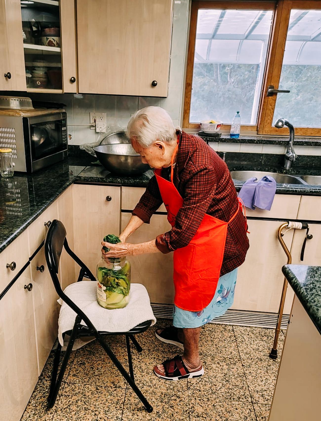 Bill's grandma putting mustard greens into pickling jar