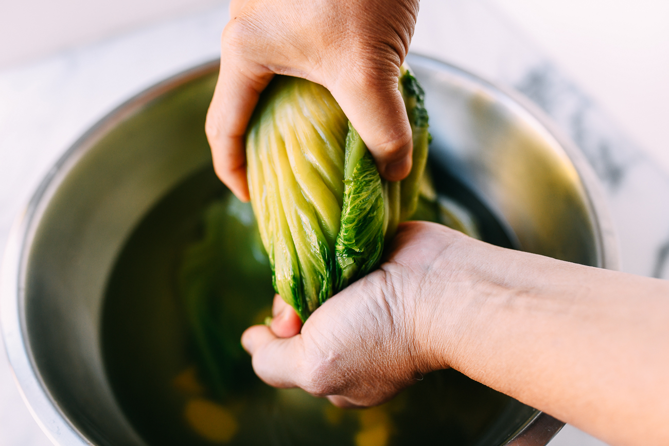 Squeezing mustard greens into smaller shape
