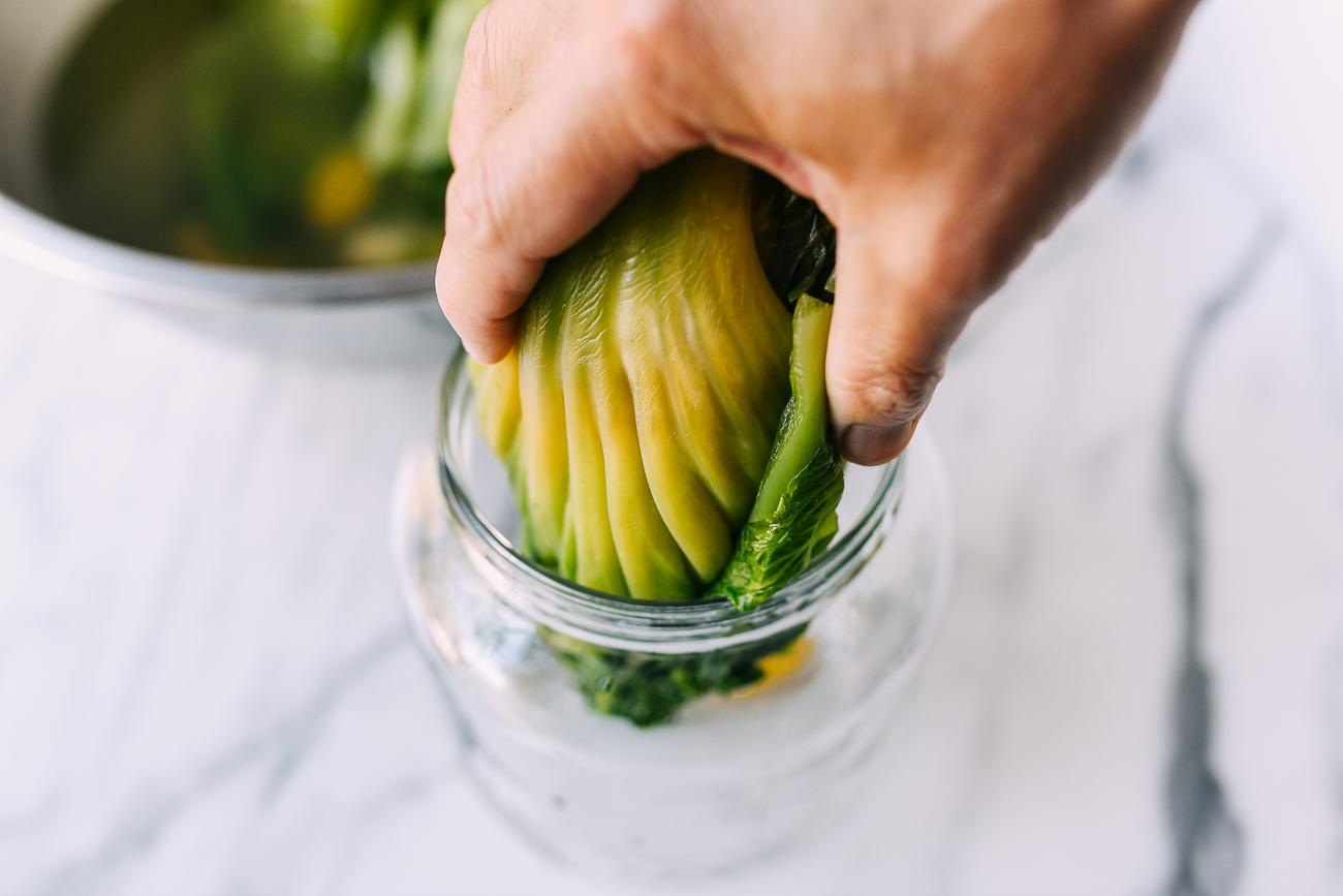 Adding mustard greens to glass jar