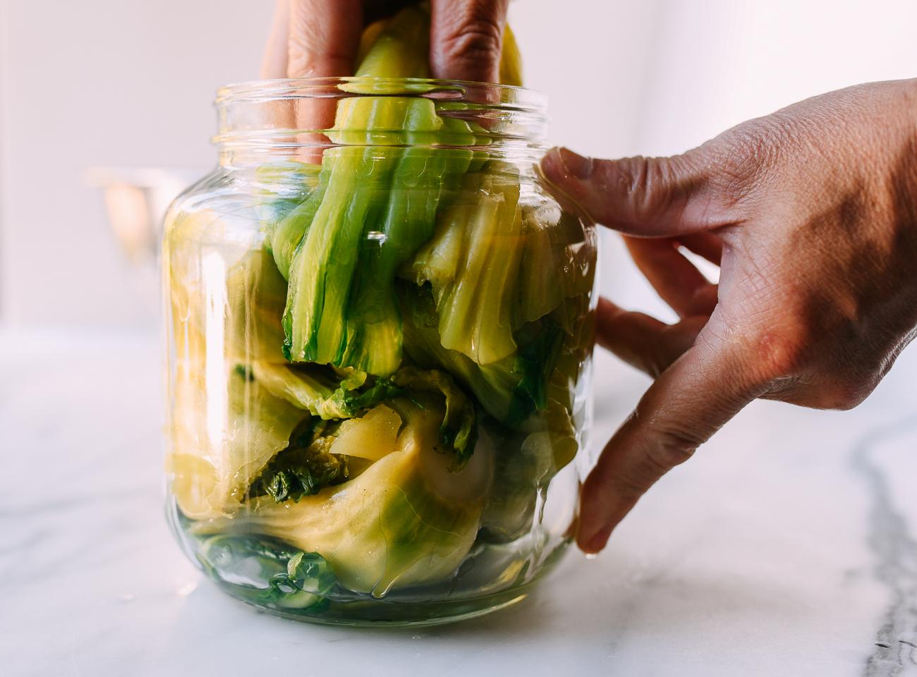 Squeezing mustard greens into pickling jar