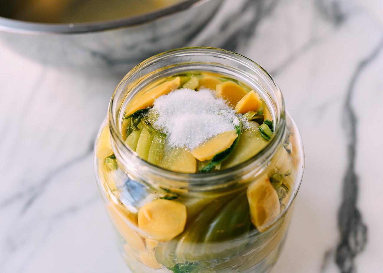 Salt and sugar on top of greens in pickling jar