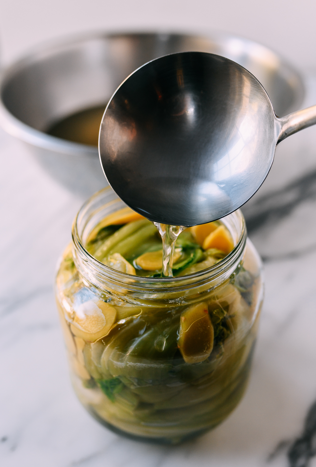Adding brine to jar of mustard greens