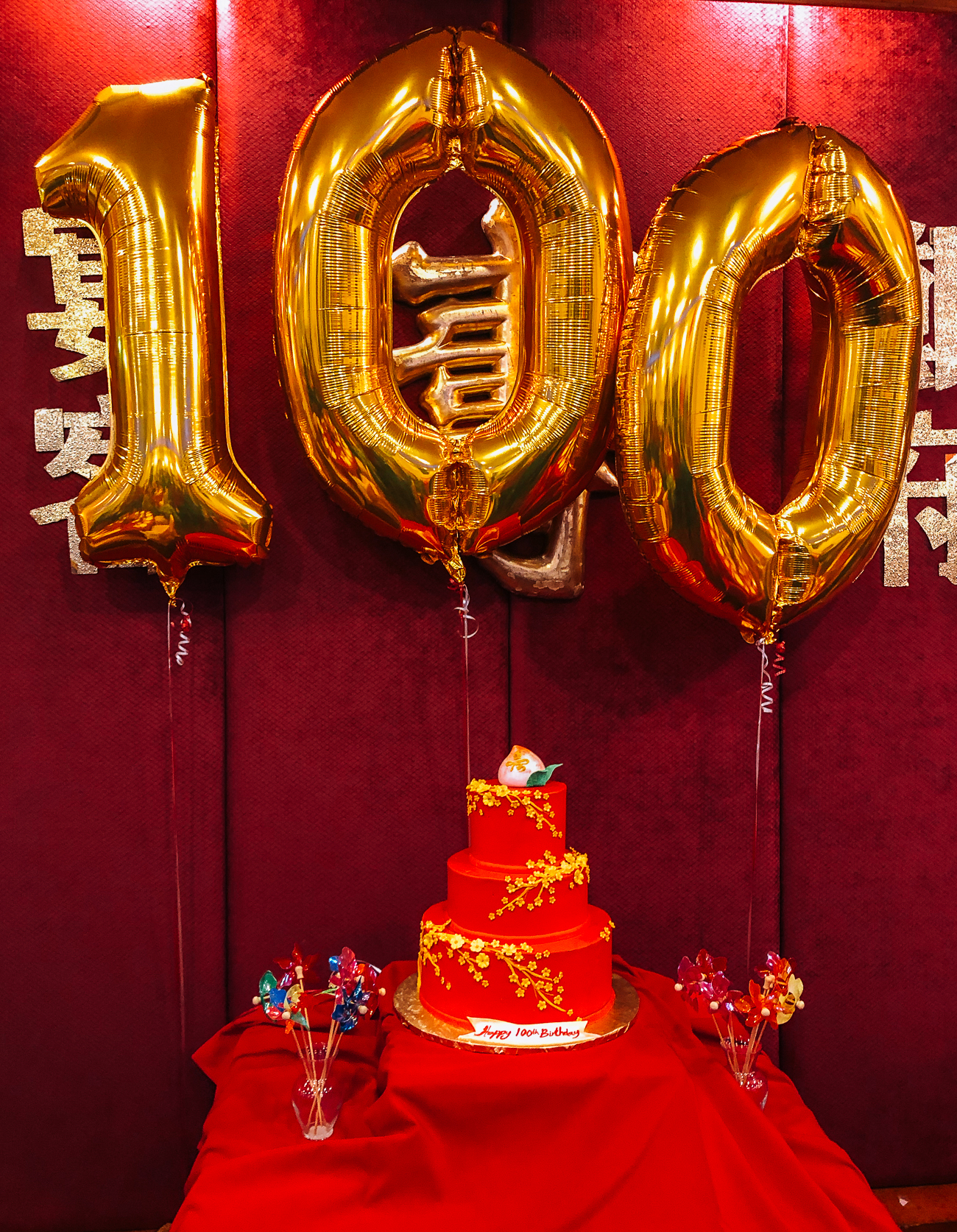100th birthday cake and balloons