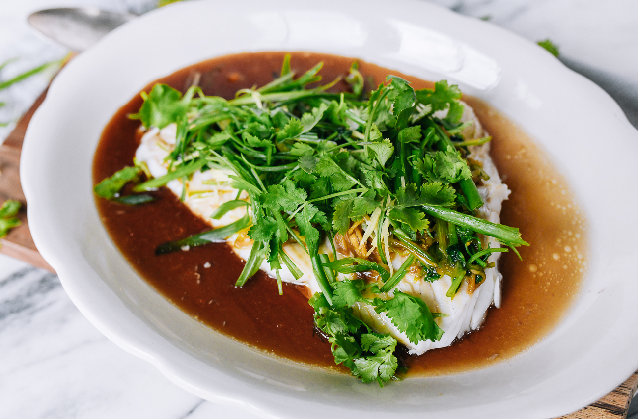 Raw aromatics over the top of sauced fish