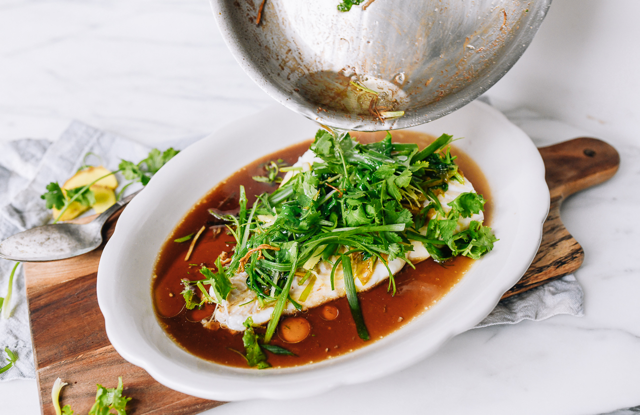 Pouring hot oil over ginger, scallions, and cilantro on Cantonese steamed fish