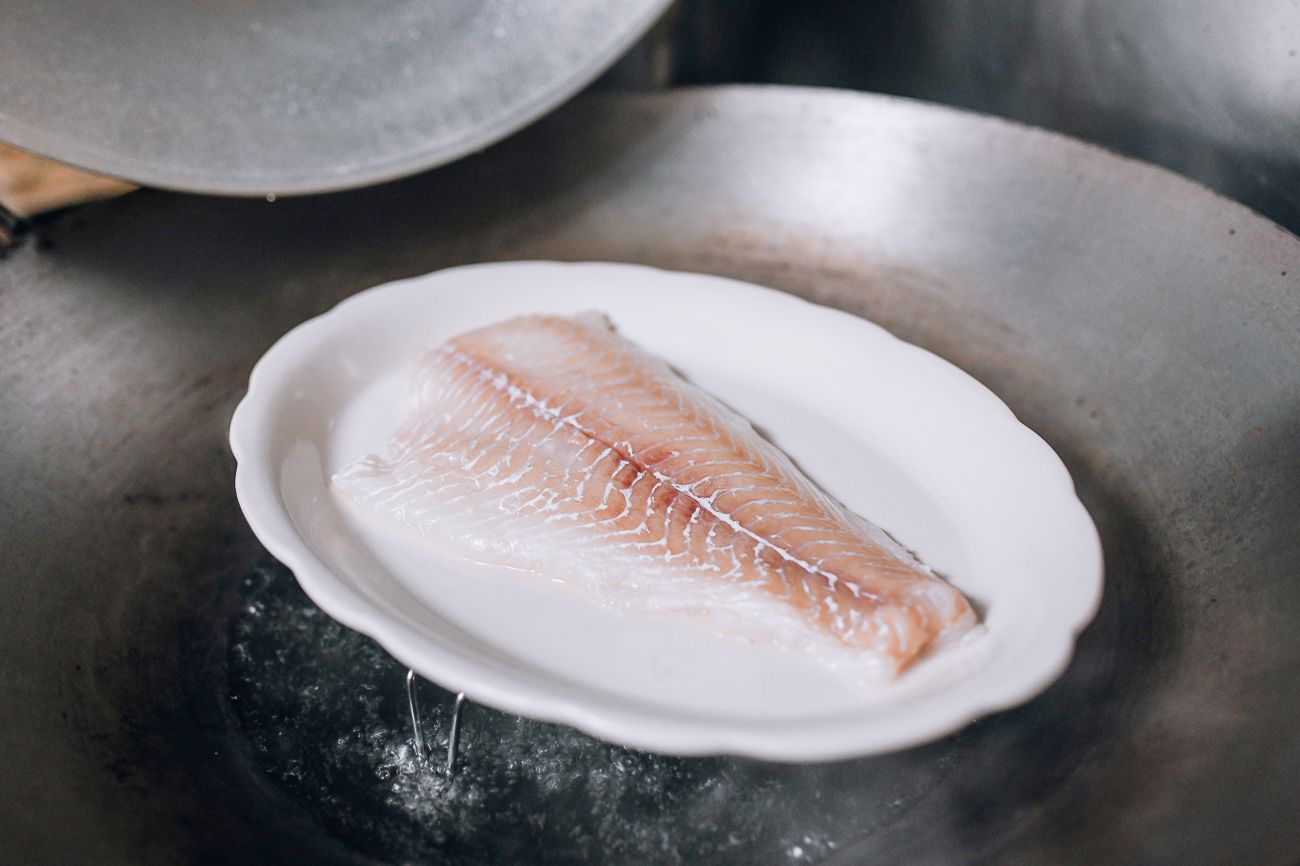 Placing plate of fish in wok to steam