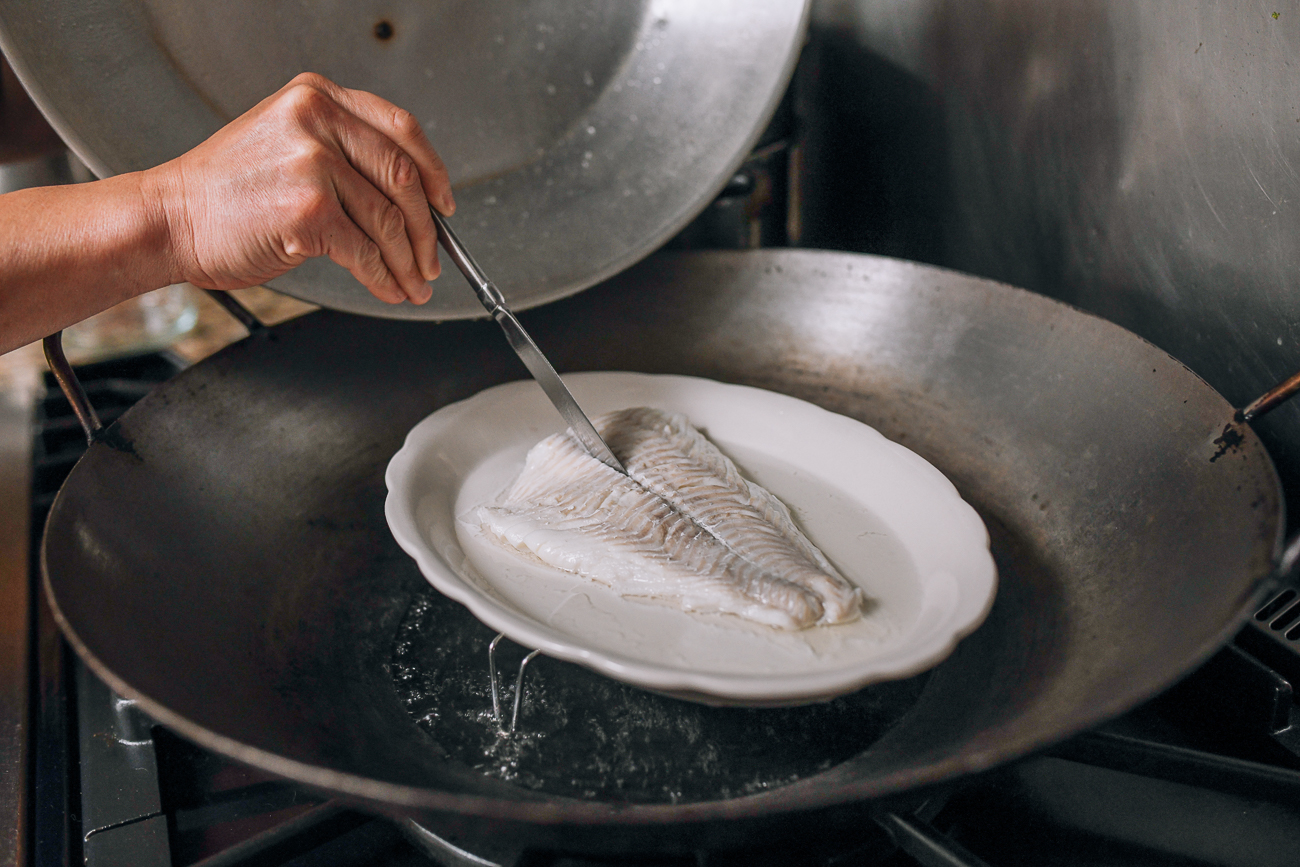 Checking fish for doneness with butter knife