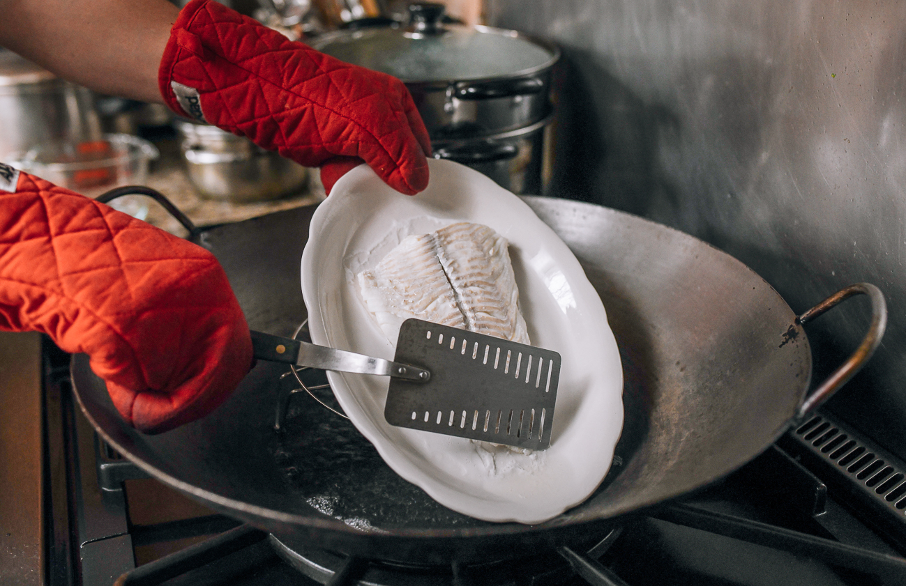 Draining liquid off plate of steamed fish