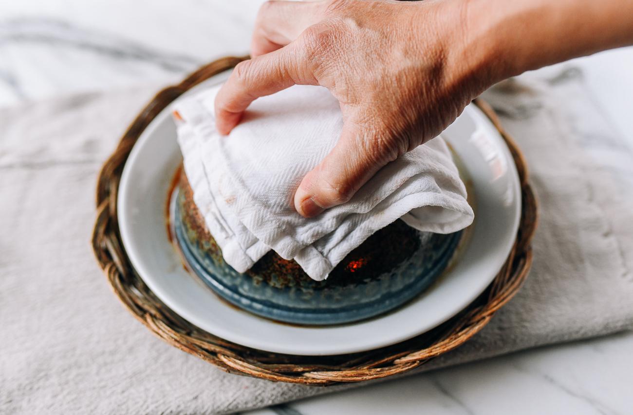 Grabbing hot bowl with a towel
