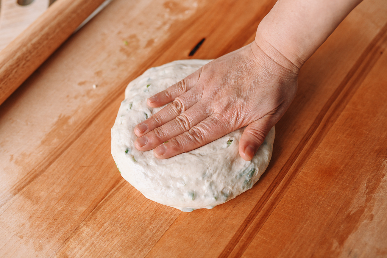 Pressing dough disc down with palm