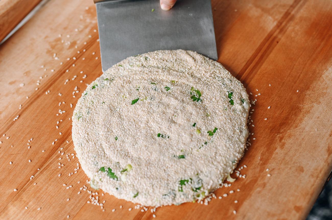 Using a bench scraper to flip dough over