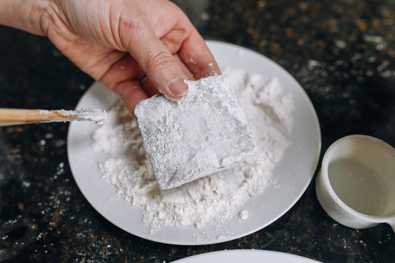 Shaking off excess flour from belt fish