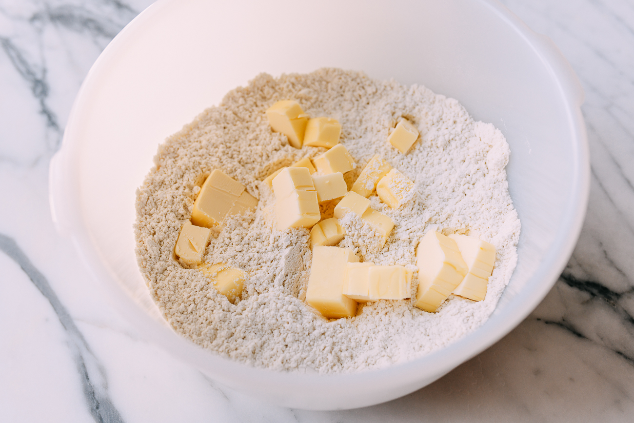 Butter cubes in bowl of flour and salt