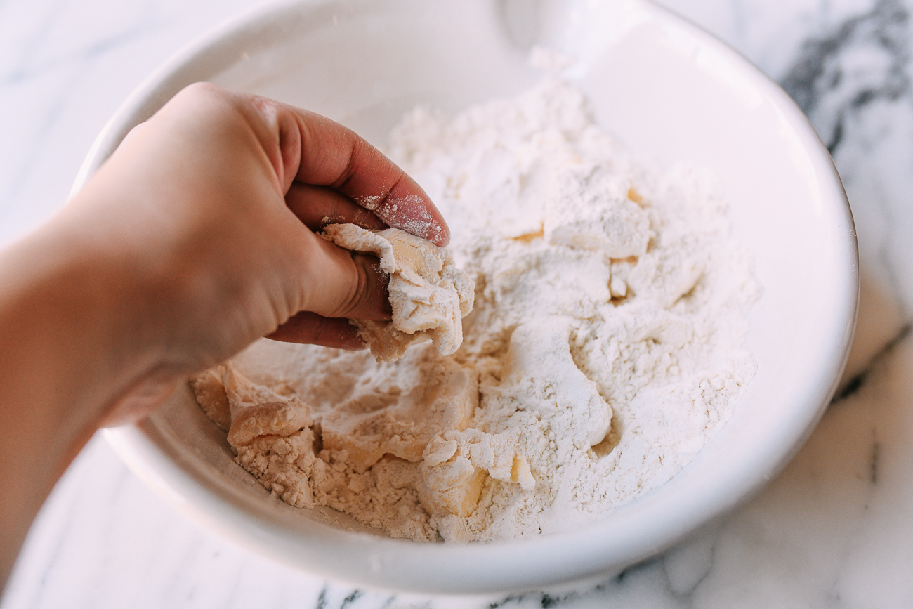 Breaking up butter in flour with hands