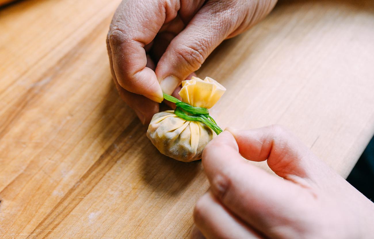Using cilantro to tie dumpling closed