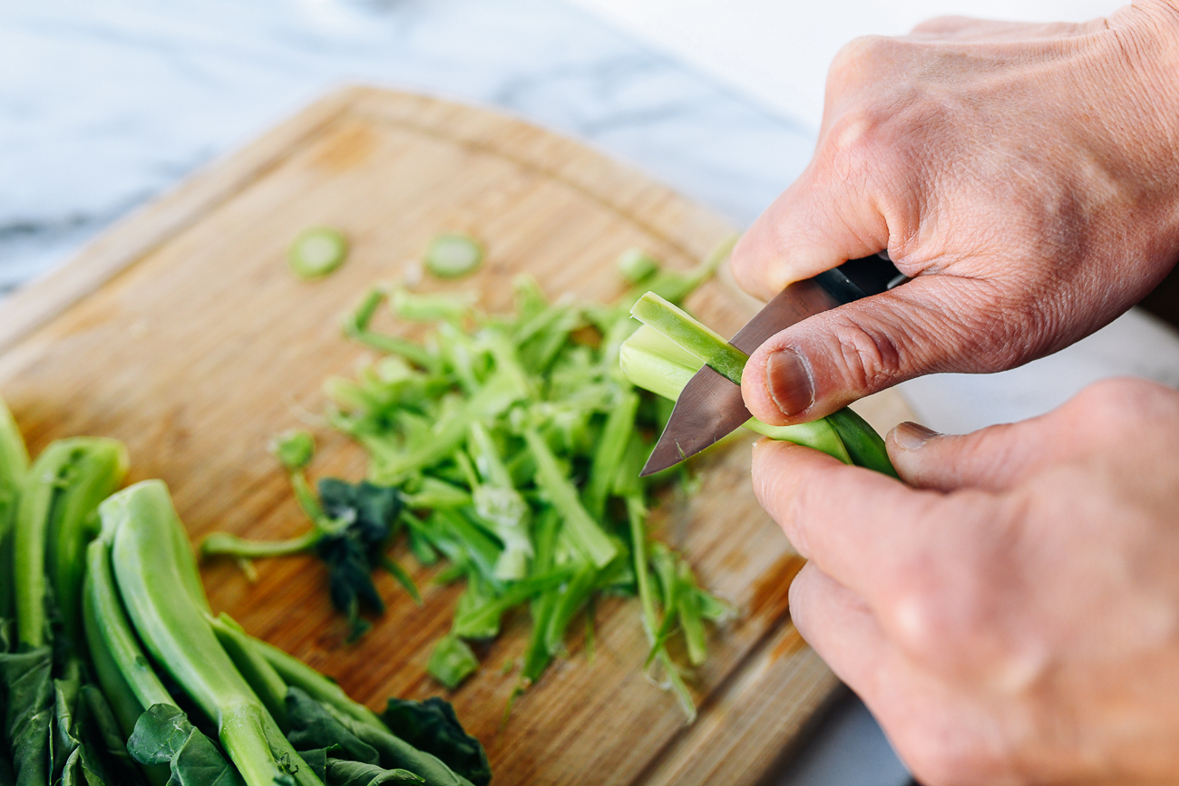 Trimming Chinese broccoli stems with a paring knife