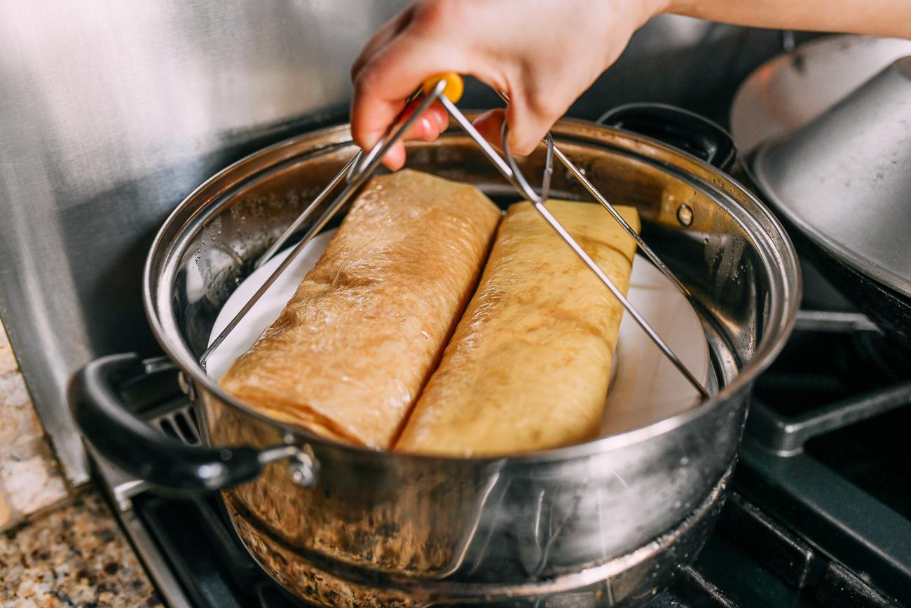 Putting bean curd sheet rolls into steamer