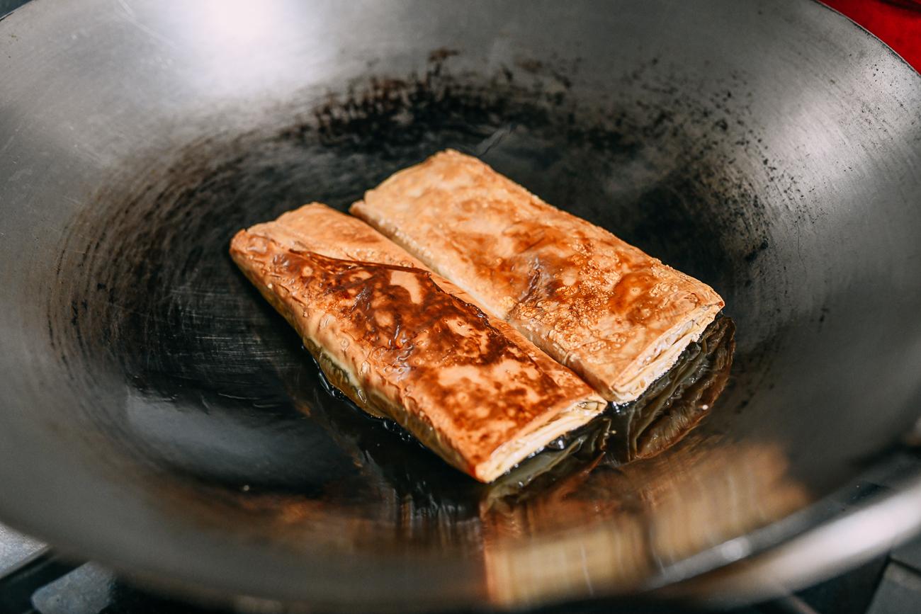 Browning bean curd rolls in wok