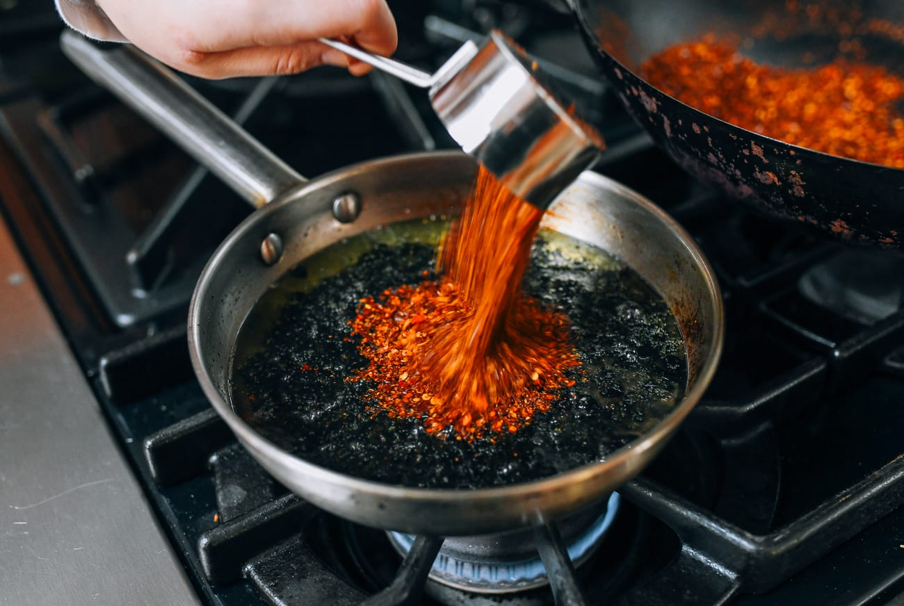 Pouring chili flakes into oil