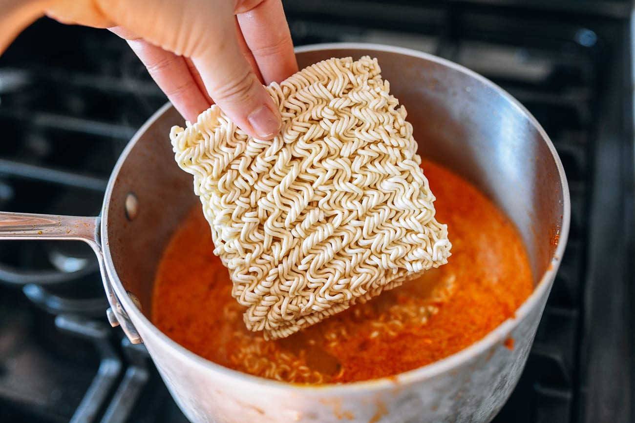 Adding instant noodles to pot of broth