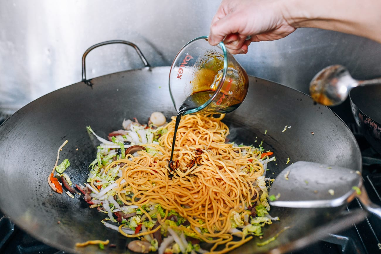 Pouring sauce mixture over lo mein noodles in wok