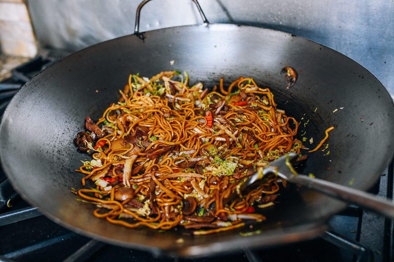 stir-frying lo mein in wok