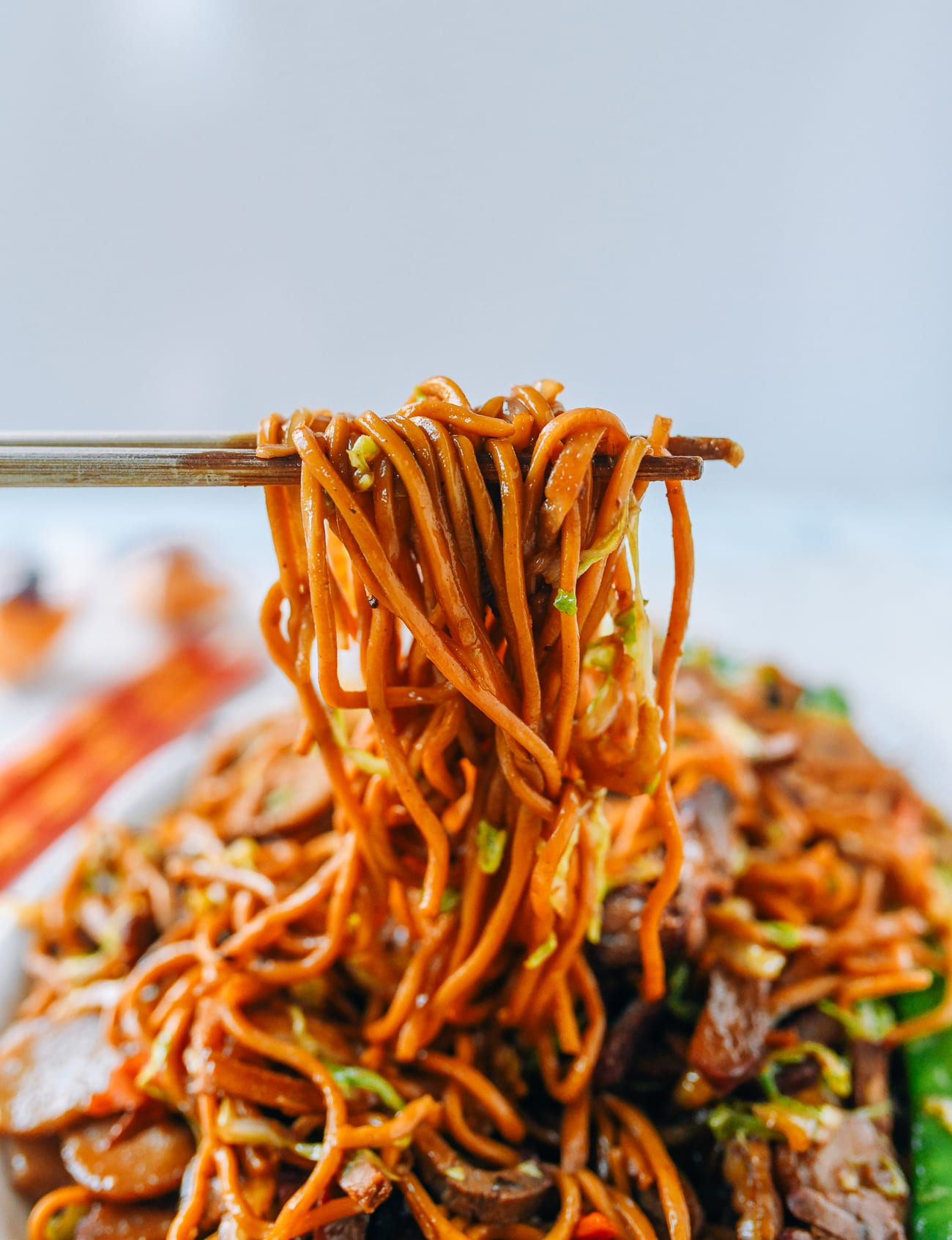 Pulling up strands of lo mein noodles with chopsticks