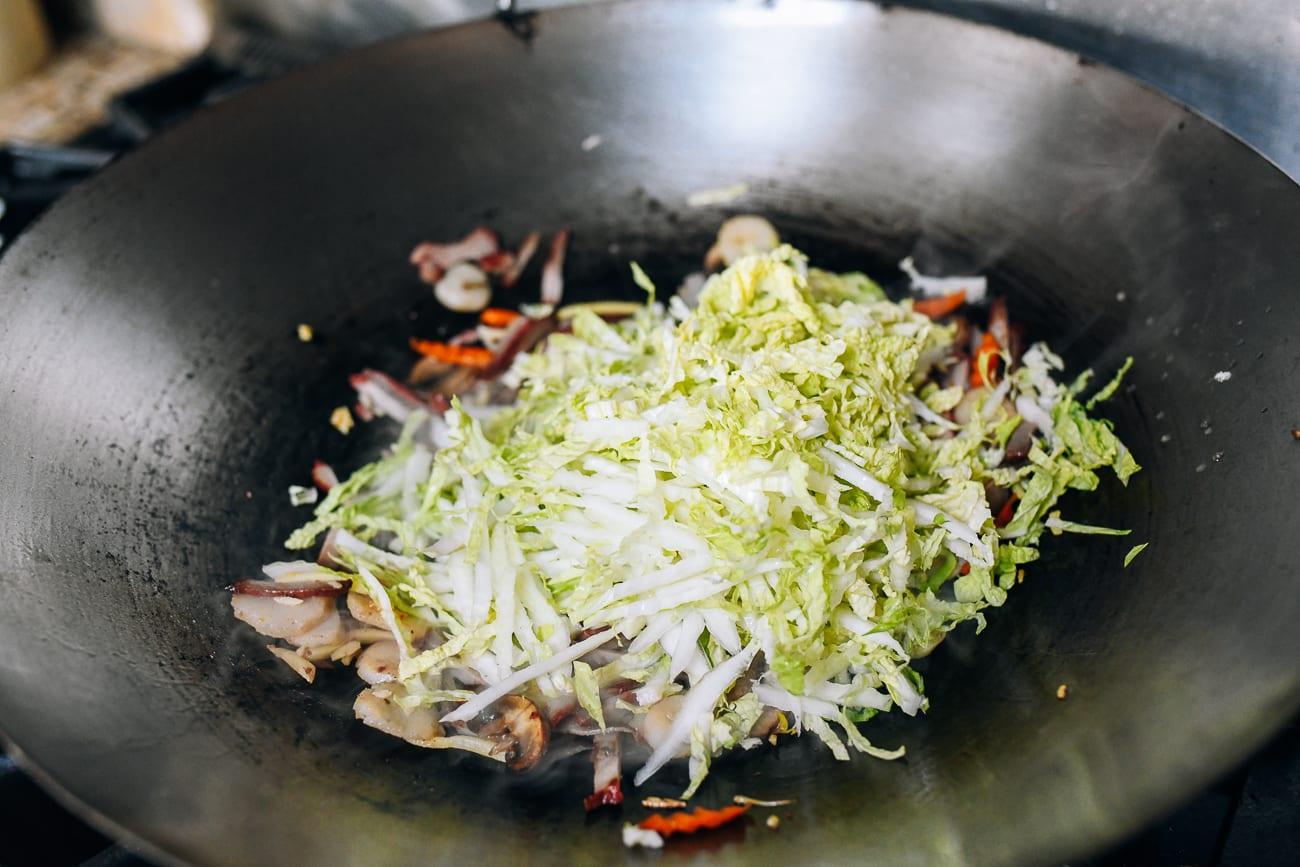 Adding shredded napa cabbage to wok