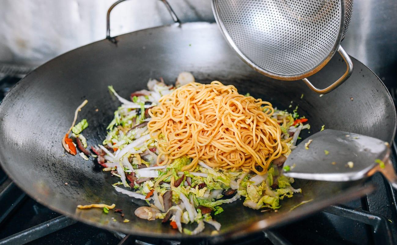 Adding lo mein noodles to wok