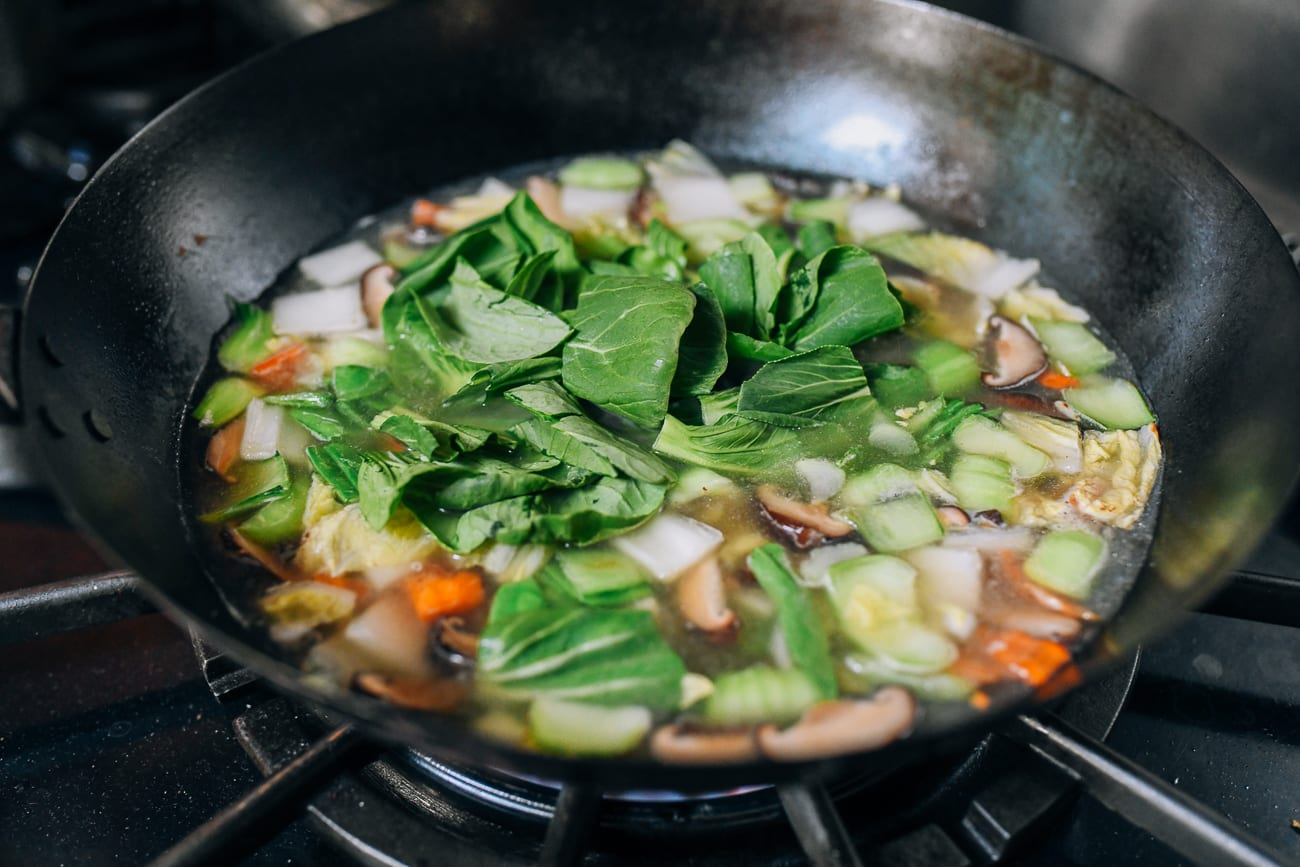 Adding leafy portions of baby bok choy to soup
