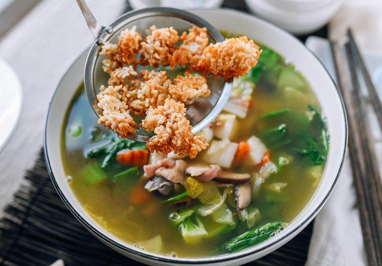 Putting crispy fried rice onto hot soup
