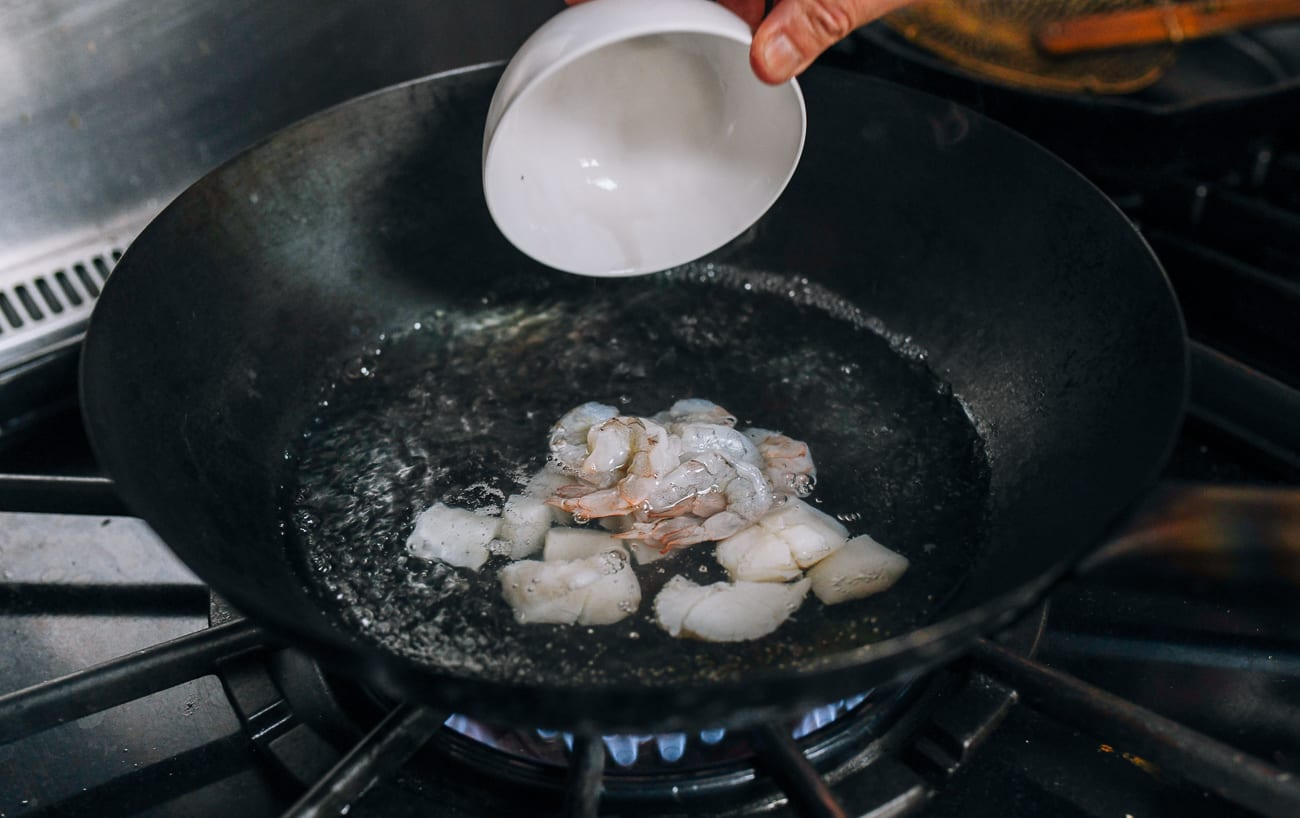 Adding shrimp and scallops to boiling water in wok