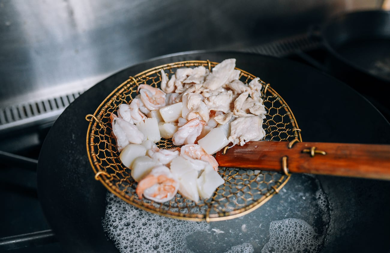 Removing blanched shrimp, scallops, and chicken from boiling water using spider strainer