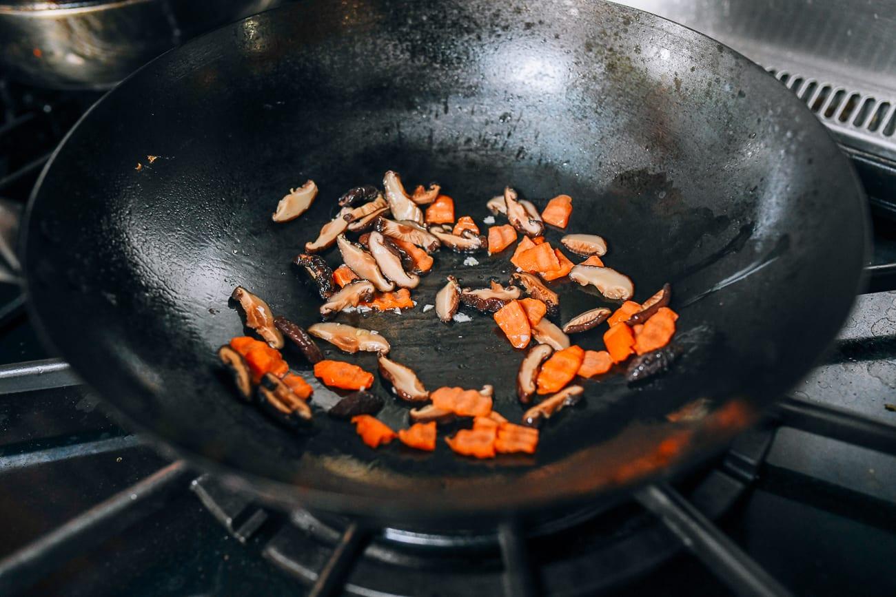 Cooking garlic, carrots, and shiitake mushrooms in wok