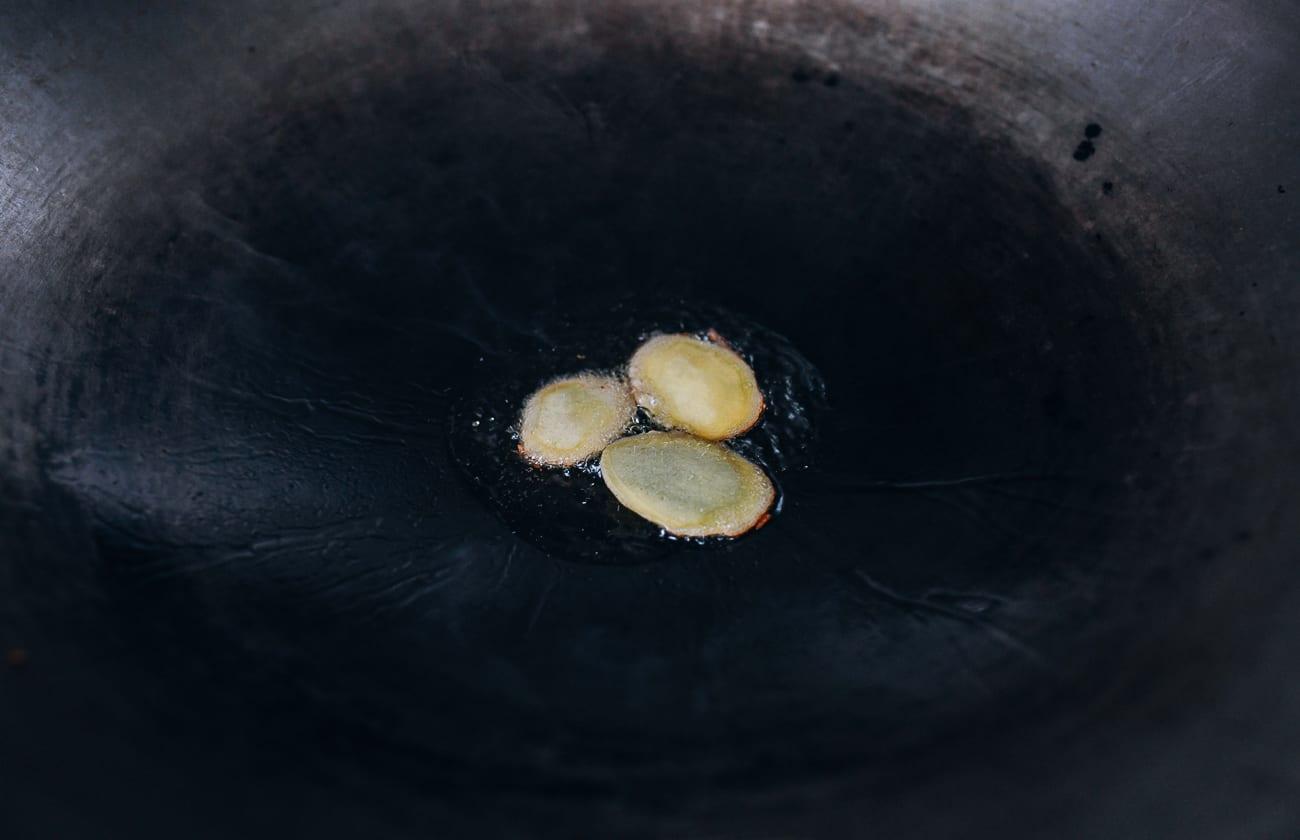 Frying ginger slices in wok