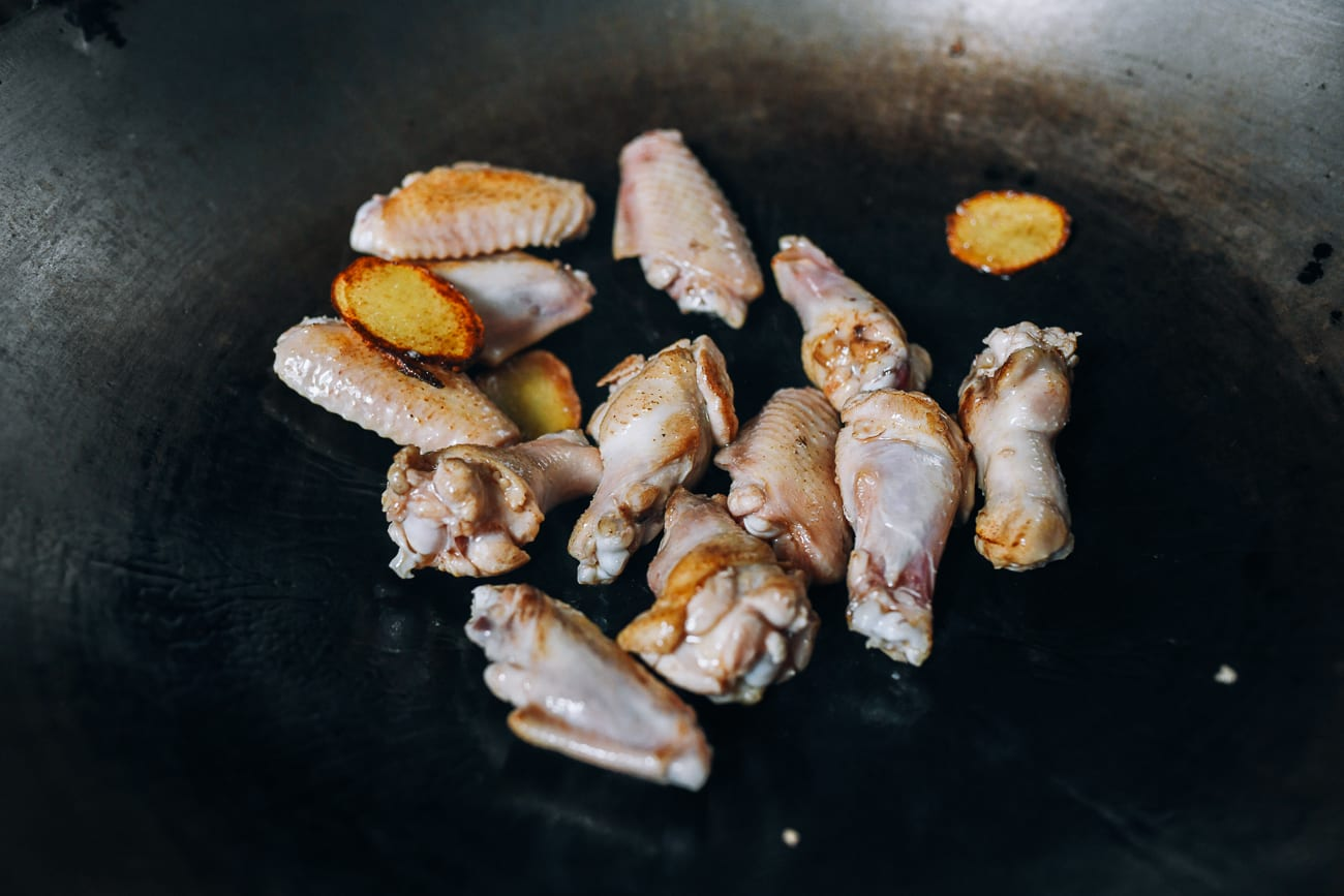 Frying chicken wing pieces with oil and ginger in wok