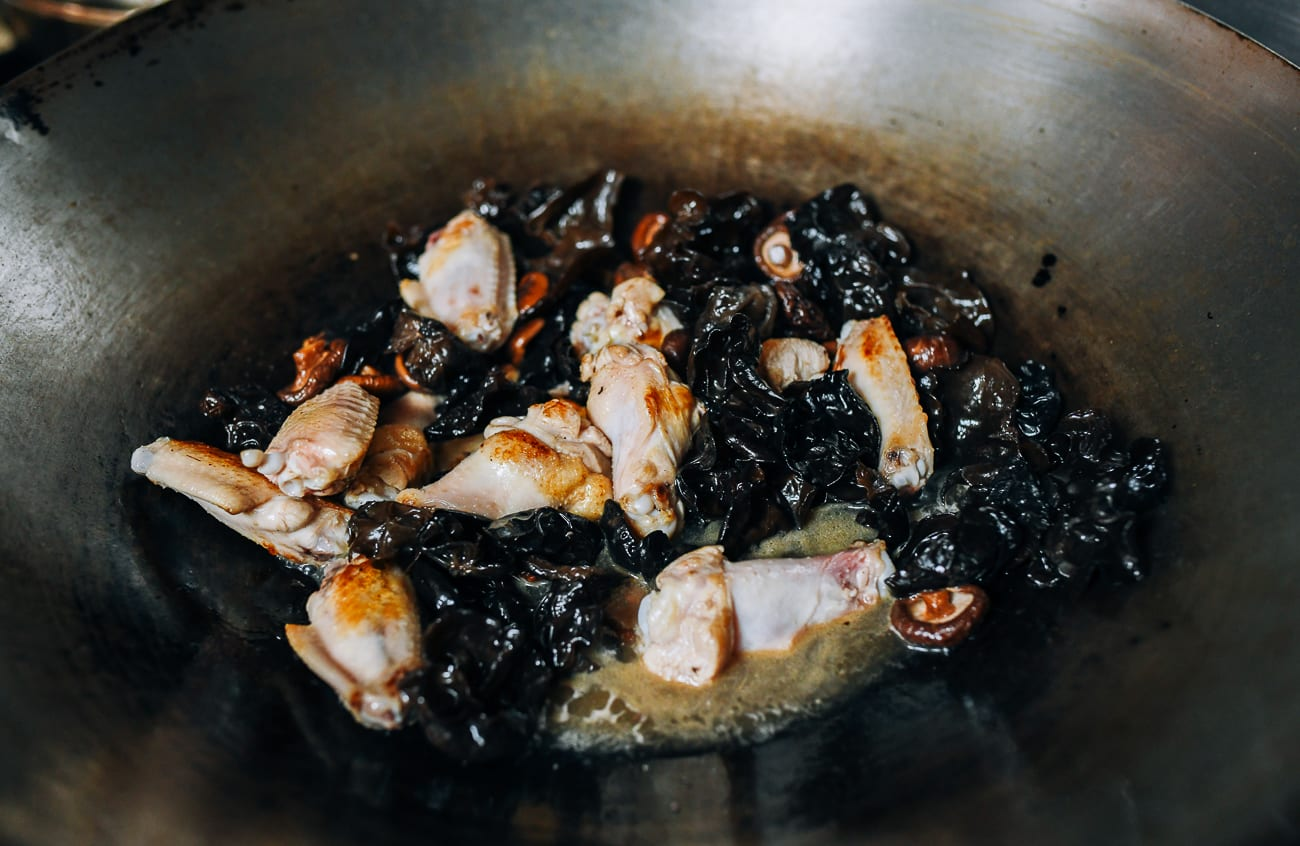 Adding braising liquid to mushrooms and chicken