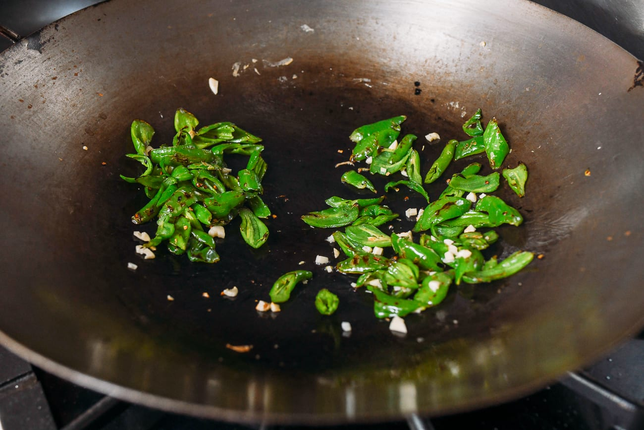 Adding peppers to wok with garlic