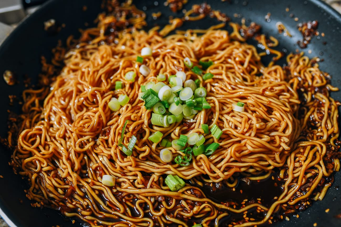 Mixing noodles in sauce with scallions