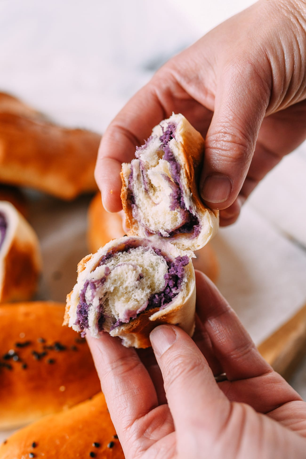 Ripping open an ube bun with two hands