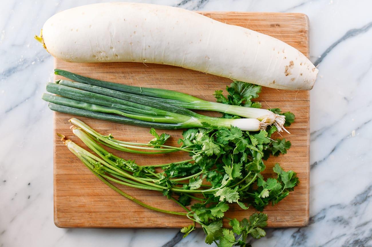 daikon radish, scallions, and cilantro on cutting board