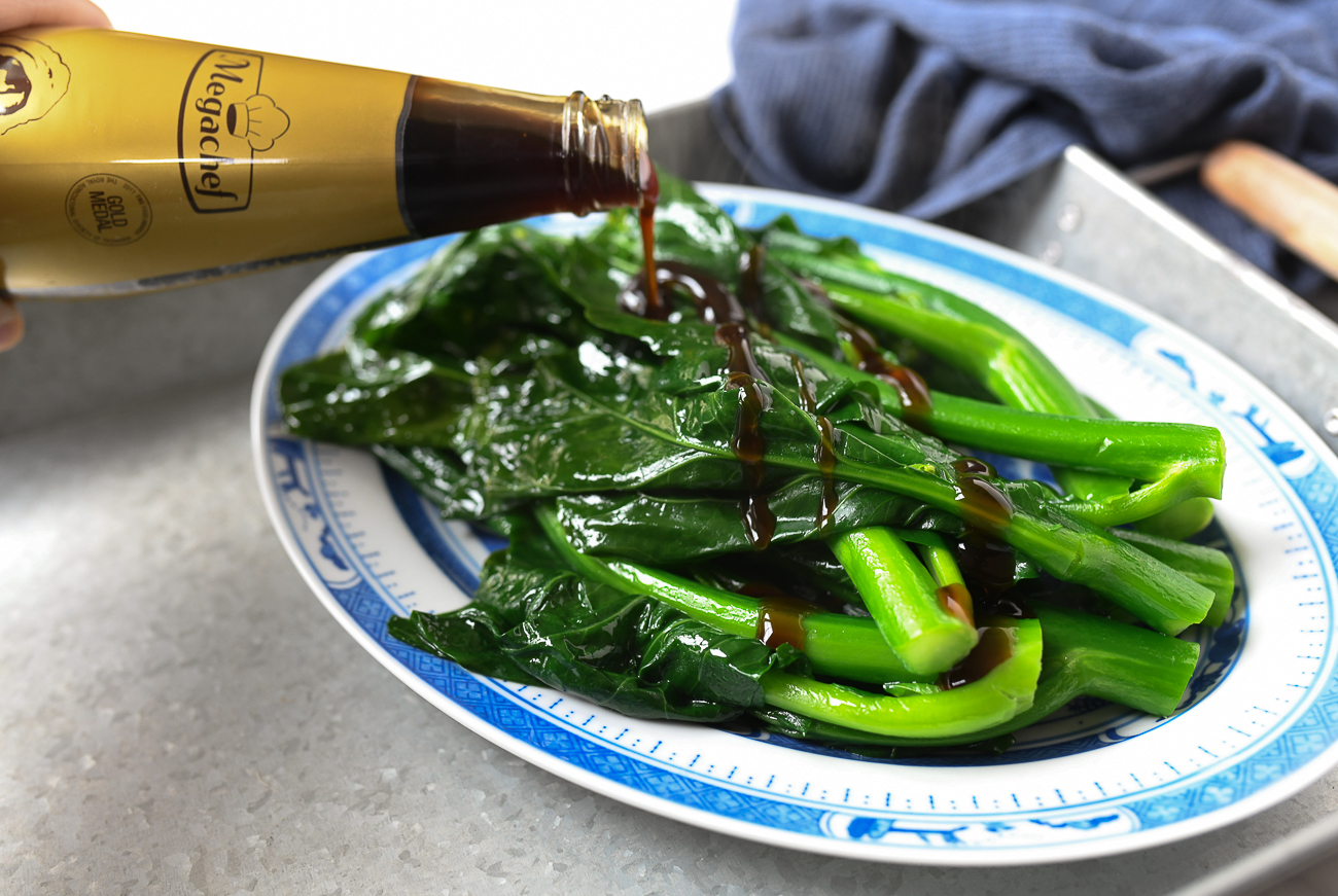 Drizzling oyster sauce over gai lan