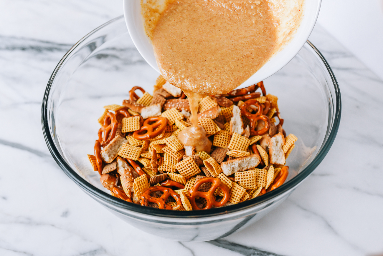 Drizzling marinade over snack mix