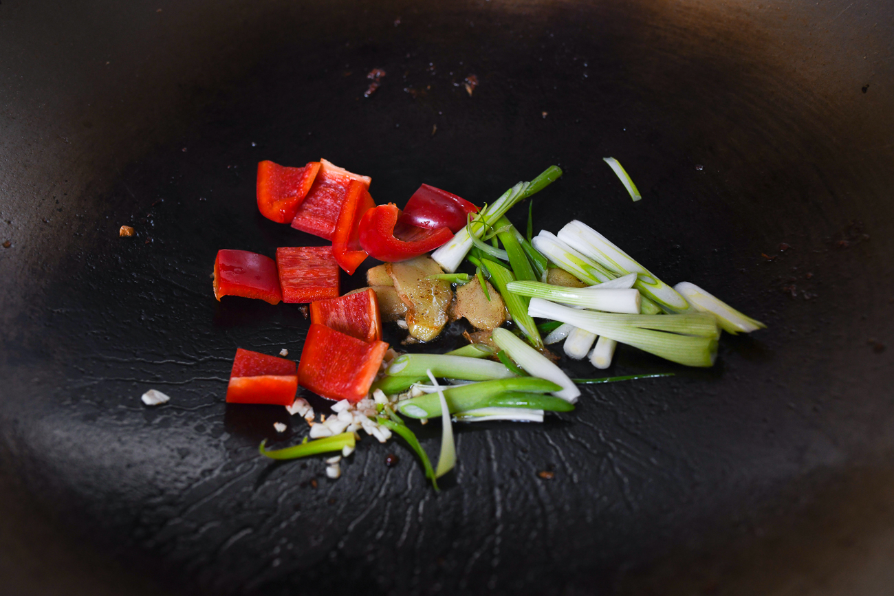 Scallions, ginger, and bell pepper in wok