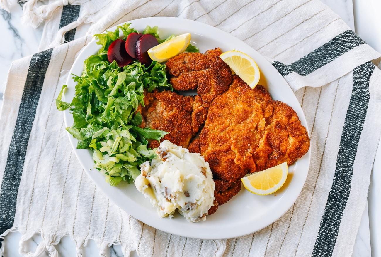 Pork schnitzel with mashed potatoes, salad, and lemon
