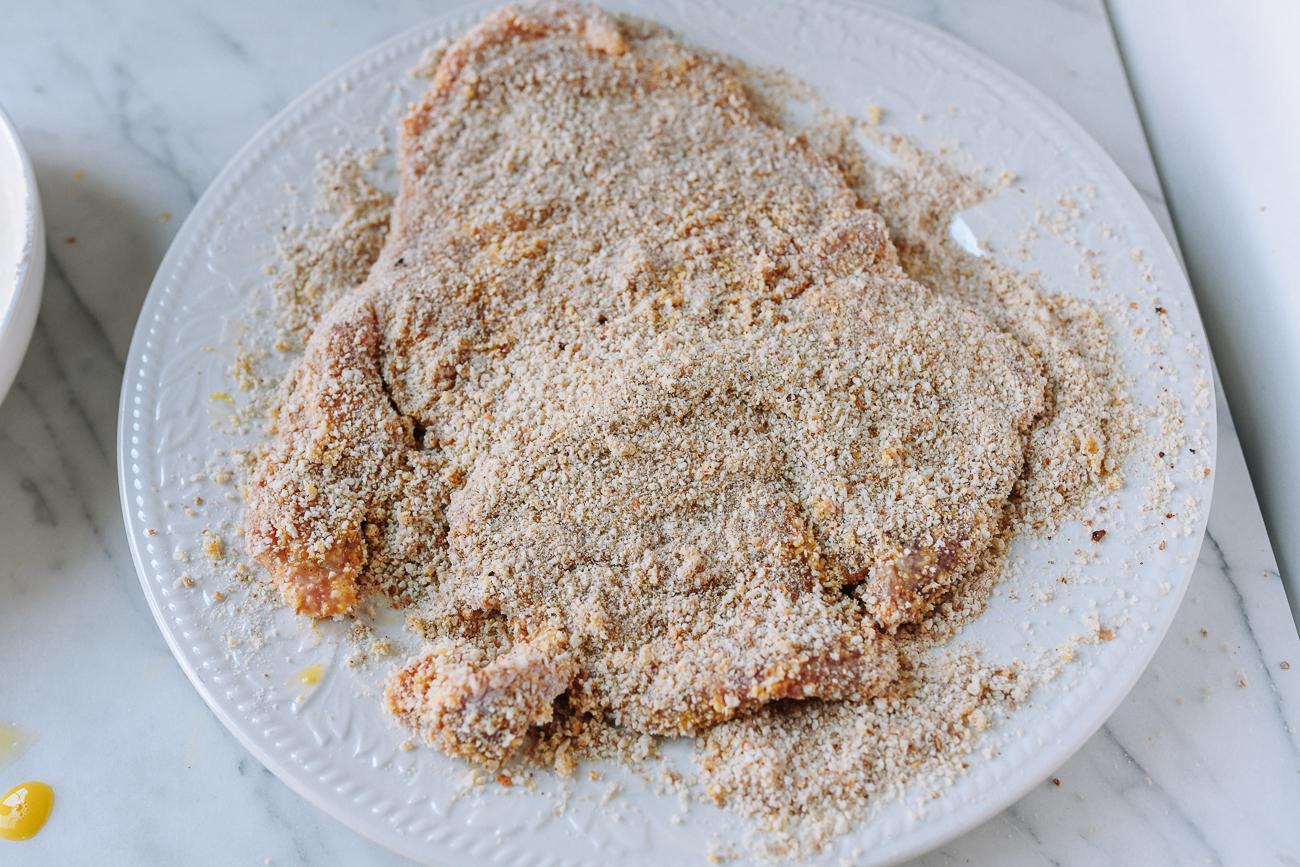 Coating pork chop in breadcrumbs