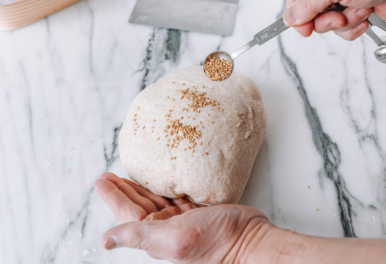 Sprinkling sesame seeds onto shaped dough
