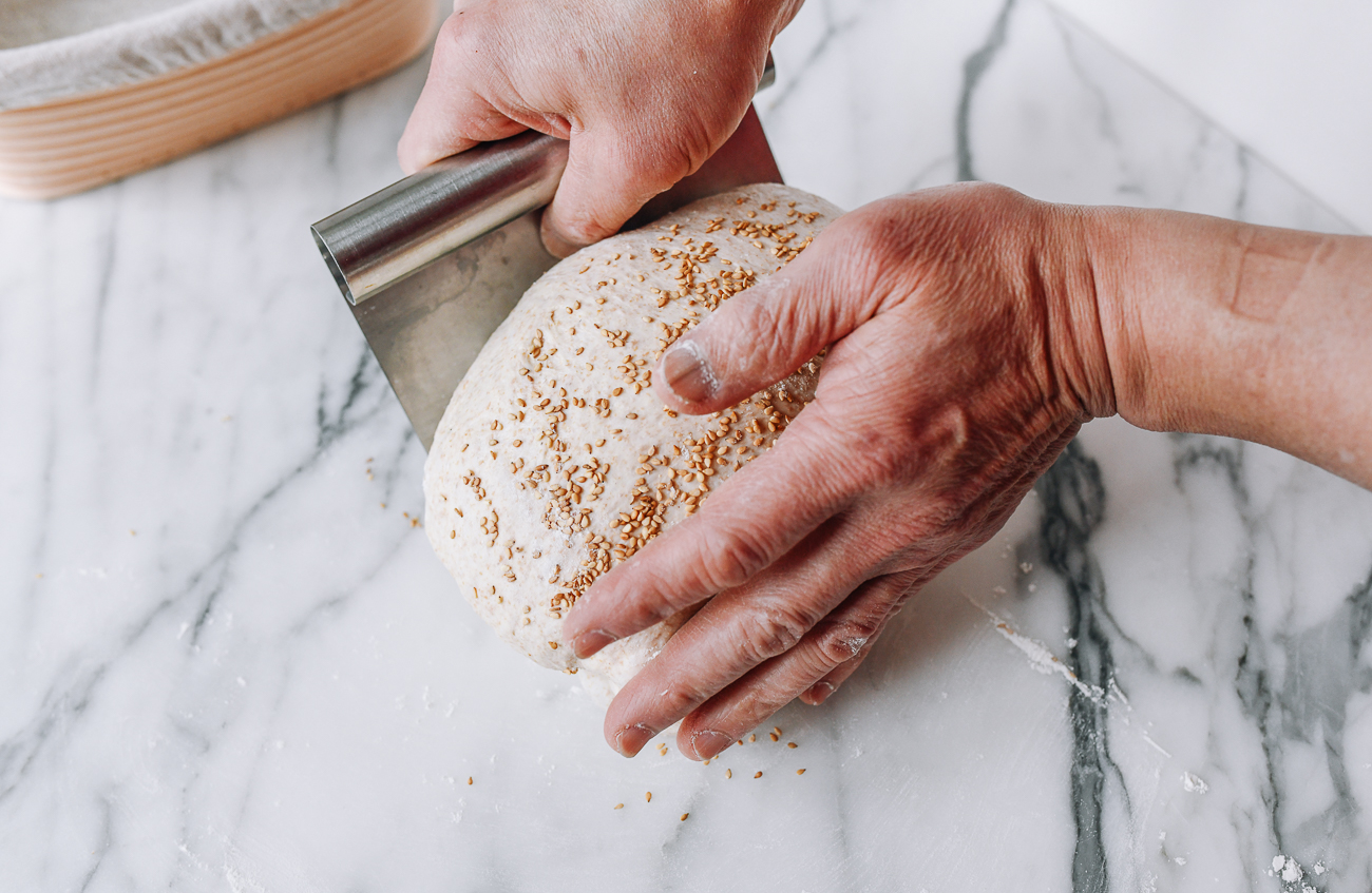 Using dough scraper to lift dough